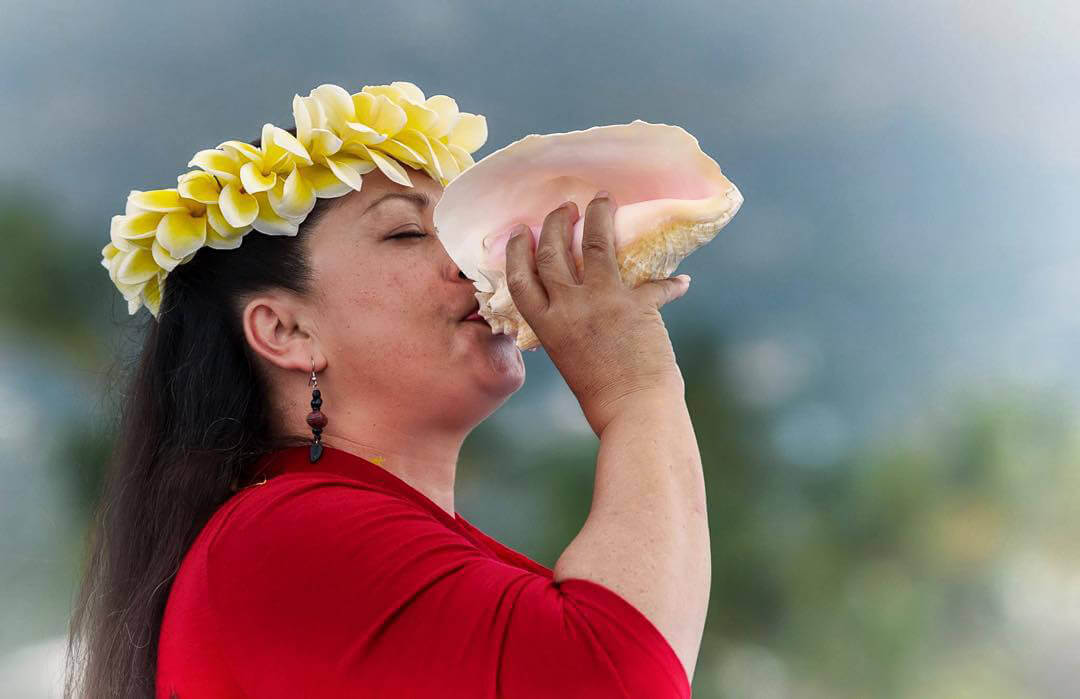 Woman Blowing on Conch Shell